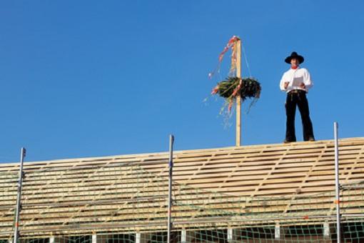 Dachdecker hält Richtspruch auf dem Dach